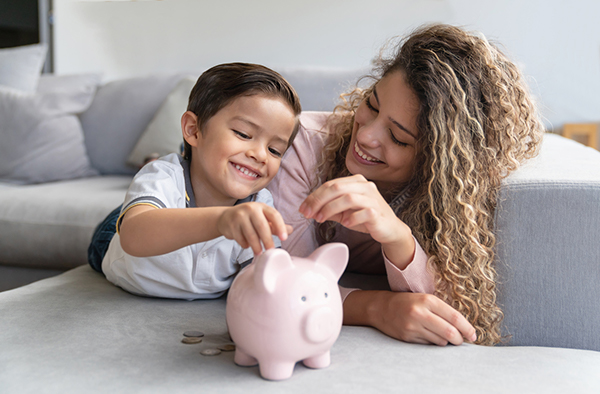Mother and child put money in a piggy bank